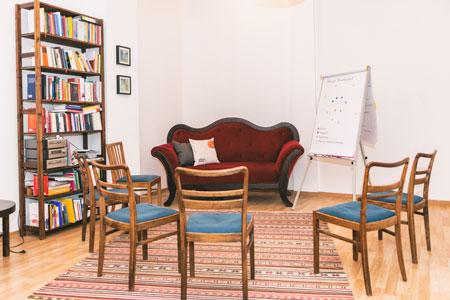 Stuhlkreis mit einem roten Sofa
