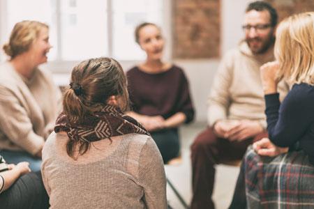 Menschen sitzen in einem Kreis und sprechen miteinander